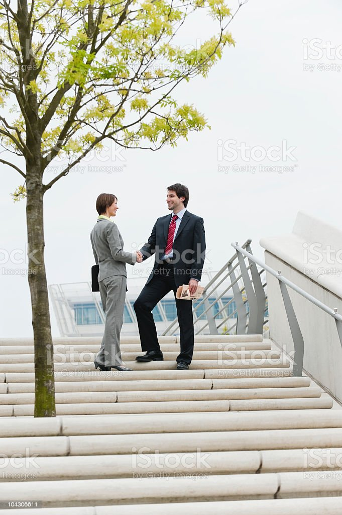 Germany, Hamburg, Business people shaking hands at stairway, smiling royalty-free stock photo