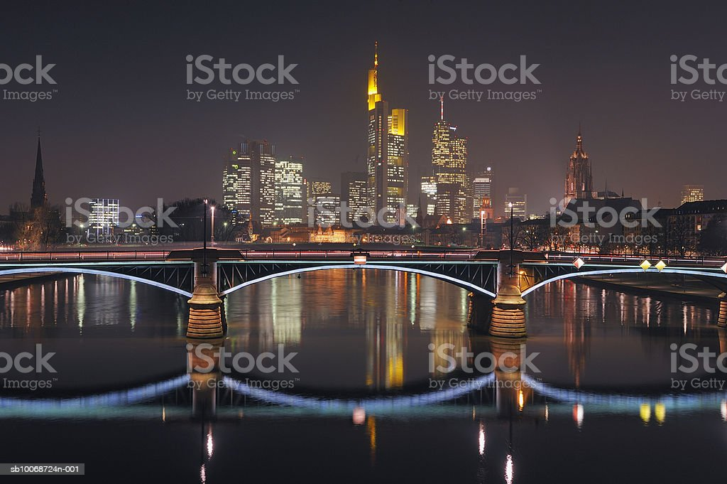 Germany, Hesse, Frankfurt, Skyline with bridge over Main River at dusk royalty free stockfoto