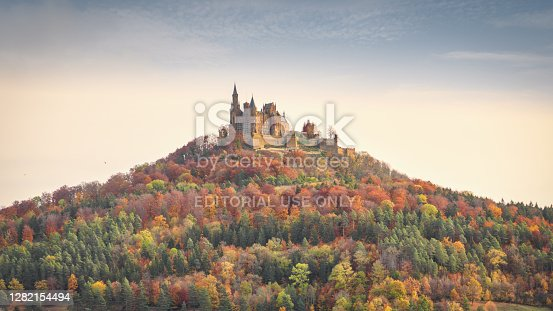 Bisingen, Baden Württemberg, Germany - October, 17th 2020: Majestic Hohenzollern Castle - Burg Hohenzollern hilltop castle panorama in moody early morning light during autumn season. Colorful surrounding autumn forest trees around the hill of Burg Hohenzollern. Swabian Jura, Baden Württemberg, Southwest Germany, Germany, Europe.