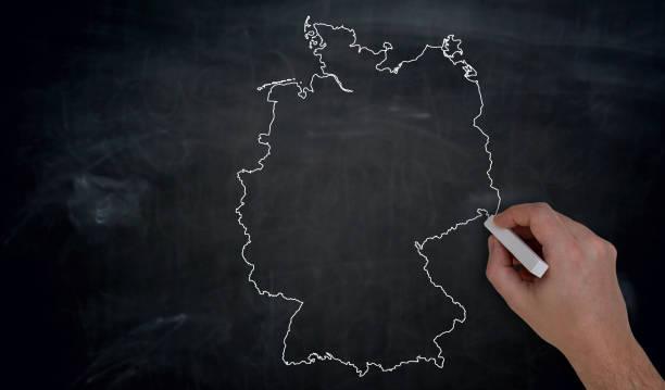 Deutschland-Karte wird von Hand auf Tafel geschrieben. – Foto