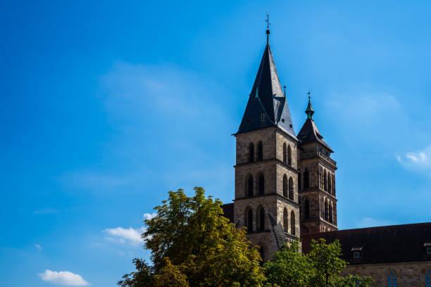 deutschland, mittelalterliche alte historische dionys oder dionysiuskirche in der innenstadt von esslingen am neckar mit zwei kirchtürmen, die durch eine brücke unter blauem himmel verbunden sind - kirchturmspitze stock-fotos und bilder