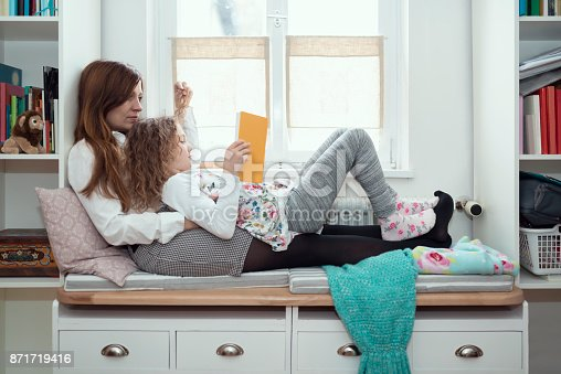 A mother hugging her daughter on a white bench in the living room. scandinavian style. the little girl is reading a book