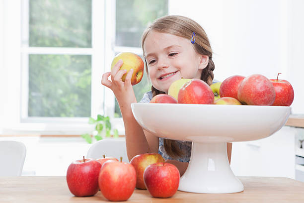 Germany, Munich, Girl (6-7) taking apple from bowl stock photo