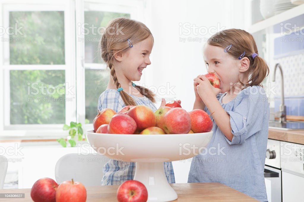Germany, Munich, girls eating apple against window royalty-free stock photo