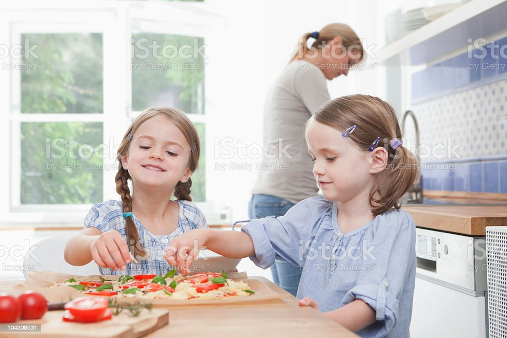 Germany, Munich, Girls (4-7) preparing food in kitchen, mother standing in background royalty-free stock photo