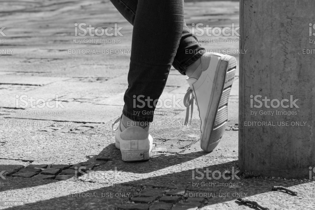 Germany, Munich, March 25, 2017, A beautiful woman is wearing white sneakers from Adidas and leans against a lantern stock photo