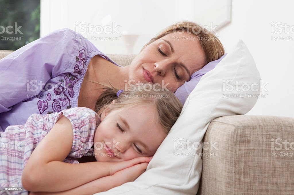 Germany, Munich, Mother and daughter (4-5) sleeping on sofa royalty-free stock photo