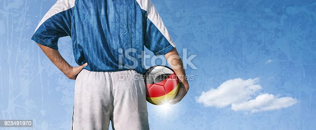 istock Germany soccer player holding ball with german flag 923491970