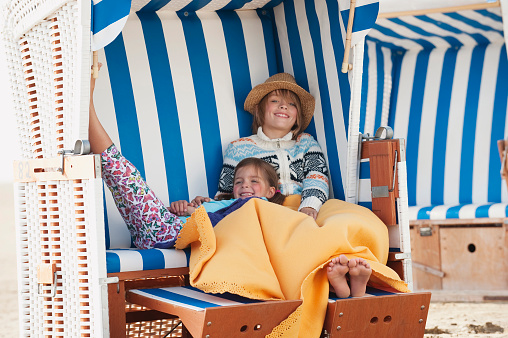 Germany, St.Peter-Ording, North Sea, Children resting on hooded beach chair