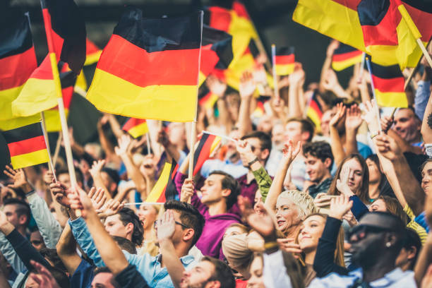 Germany supporters waving their flags on a stadium Large group of people waving Germany flags while standing on stadium bleachers. germany stock pictures, royalty-free photos & images