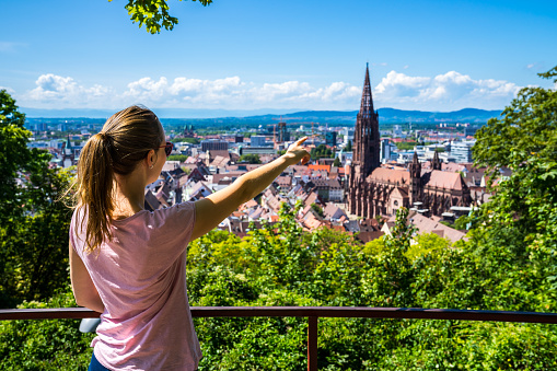 Germany, Young Blonde beauty girl standing above roofs of city freiburg im breisgau historic district and popular muenster cathedral in summertime with blue sky