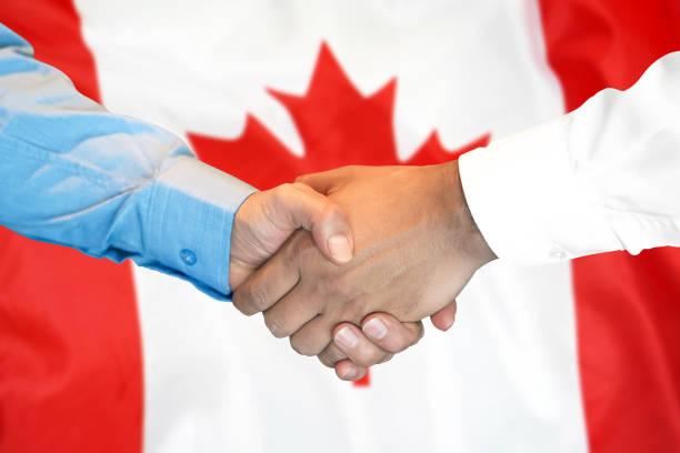 Germanyhandshake auf Kanada-Fahnenhintergrund. – Foto
