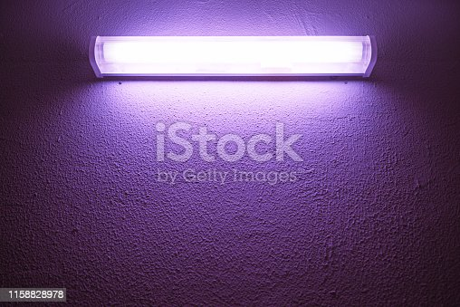 Germicidal ultraviolet lamp glows on a rough wall