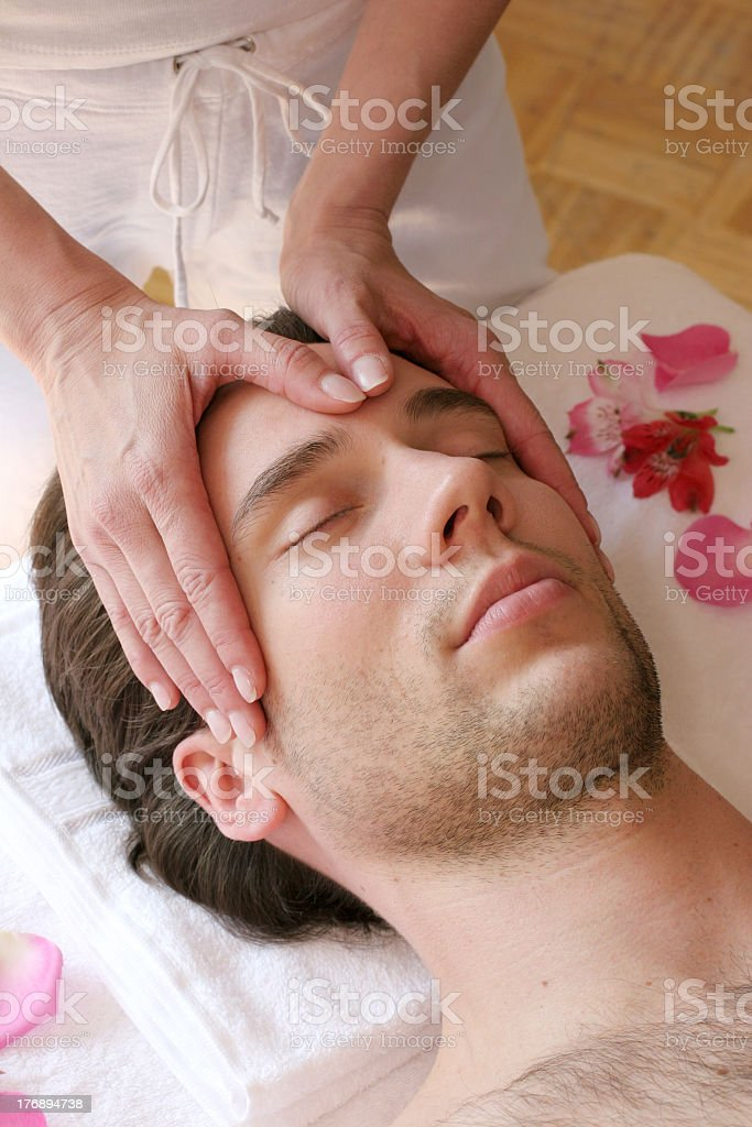 Gesichtsmassage with a young man's head being hand massaged stock photo