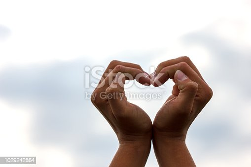 istock gesture hands heart of on backdrop of the sky 1029242864