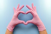 The heart, figure built from the hands in pink rubber medical gloves on a blue background.