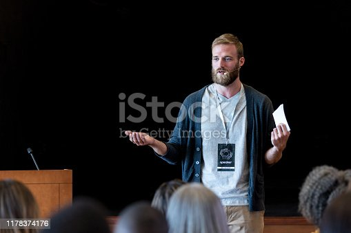 As he gestures to emphasize his point, the mid adult male hipster speaks to the expo audience during one of the break out sessions.