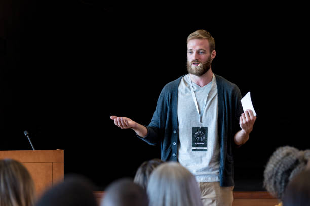 Gesturing to make point, mid adult hipster speaks to audience As he gestures to emphasize his point, the mid adult male hipster speaks to the expo audience during one of the break out sessions. college fair stock pictures, royalty-free photos & images