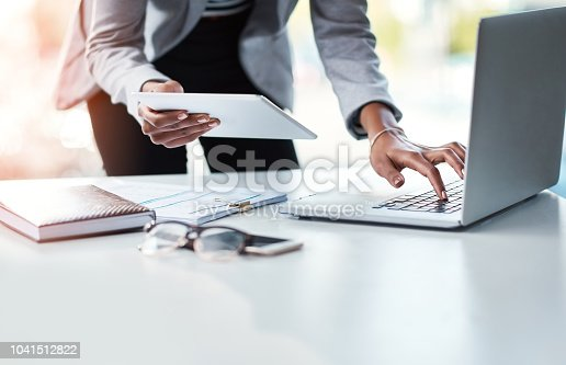 Cropped shot of a businesswoman using a laptop and digital tablet at her desk in a modern office