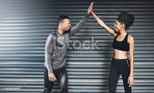 Shot of a sporty young couple giving each other a high five against a grey background