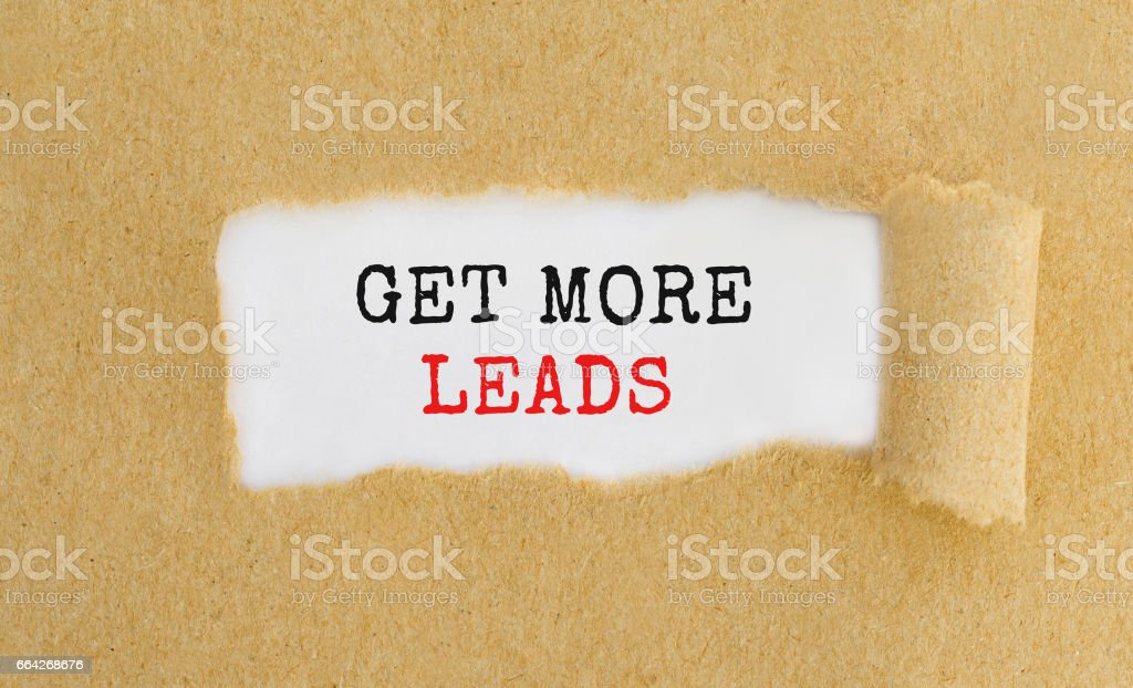 Get More Leads appearing behind ripped brown paper. stock photo