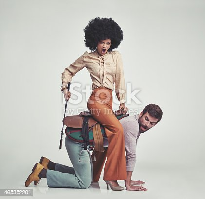 A studio shot of an attractive woman in 70s wear riding a handsome man wearing a saddle while using a riding crop