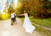 bride after groom with woman on motor riding it.