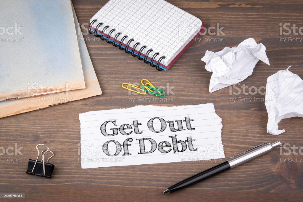 Get out of Debt. Papierblatt aus dem Booklet auf dem Holztisch – Foto