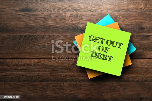 Get Out Of Debt, the phrase is written on multi-colored stickers, on a brown wooden background. Business concept, strategy, plan, planning.