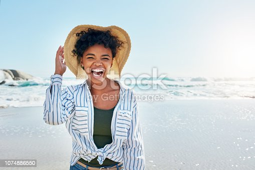 Shot of a young woman enjoying a day at the beach