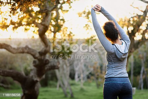 Rearview shot of a young woman stretching before a run outdoors