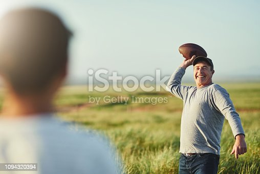Shot of father throwing a football to his son on a field