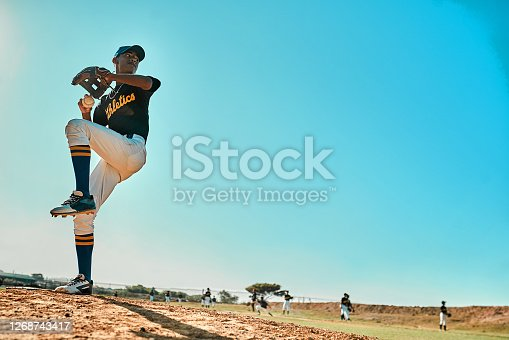 Shot of a young baseball player pitching the ball during a game outdoors
