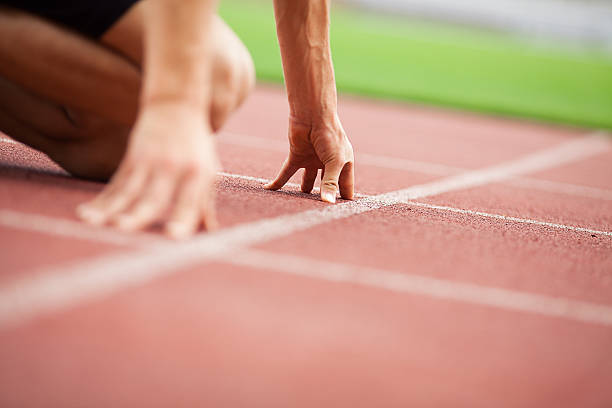 Get ready... Close up of a professional athlete assuming the start position, preparing to run. starting line stock pictures, royalty-free photos & images