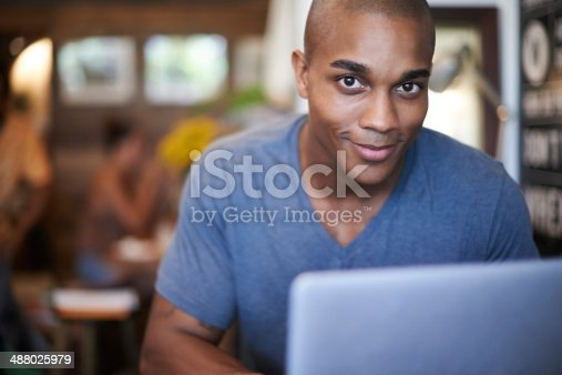 Cropped shot of a handsome young man using his laptop in a coffee shop