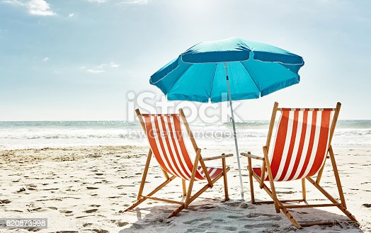 Still life shot of two deck chairs under an umbrella on the beach