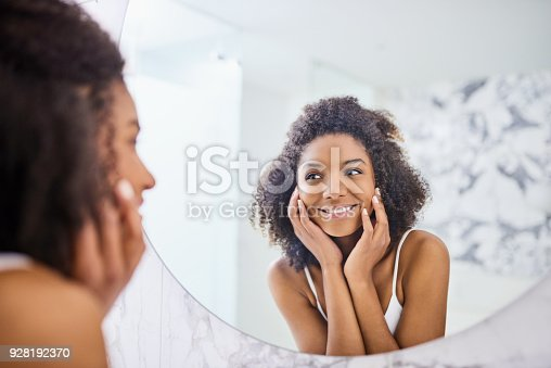 Shot of an attractive young woman admiring her face in the bathroom mirror