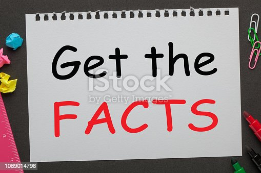 Get the Facts written on notebook paper and office supplies on black background. Business concept.