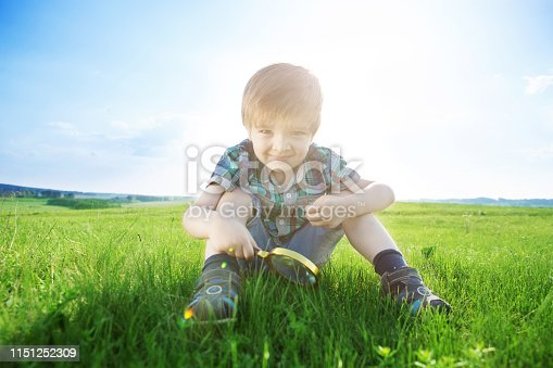 Get to know the world. Everything is incredible near you. Happy little boy exploring nature with magnifying glass at the day time