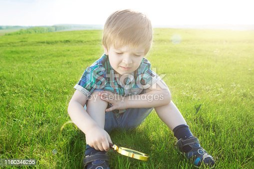 Get to know the world. Everything is incredible near you. Young caucasian boy exploring garden during summer time with his magnifier.