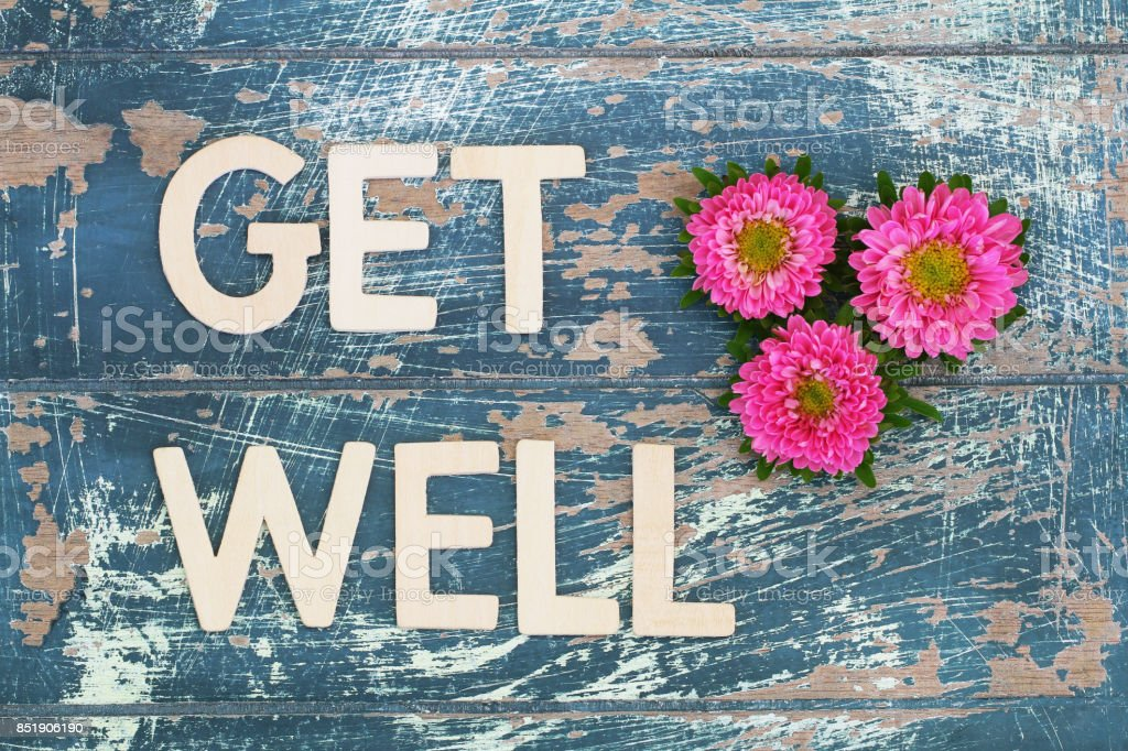 Get well written on rustic wooden surface and pink daisies stock photo