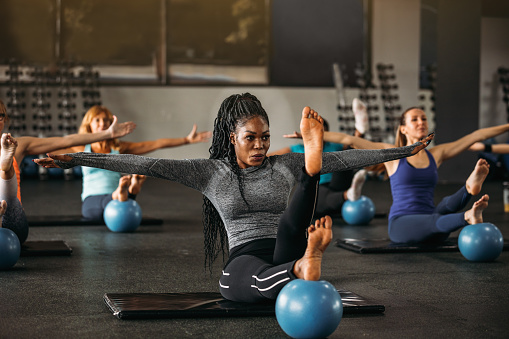 Group of women working balance exercise in the gym.