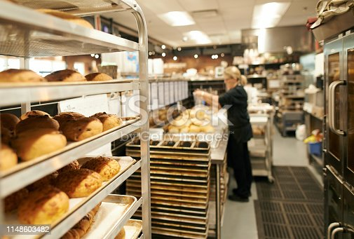 Shot of a rack of freshly baked goods with a woman working in the background at a bakery