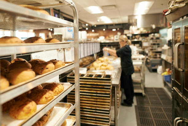 Get your carb fix here Shot of a rack of freshly baked goods with a woman working in the background at a bakery baking bread stock pictures, royalty-free photos & images