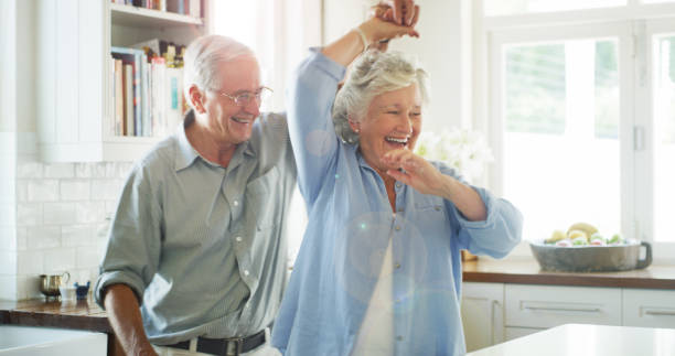 Get your groove back? Or never lose it at all Shot of a happy senior couple dancing together at home dancing stock pictures, royalty-free photos & images