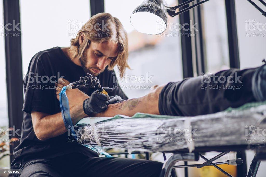 Getting a new leg tattoo stock photo