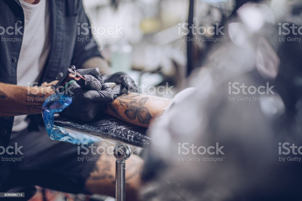 Getting a tattoo on arm stock photo