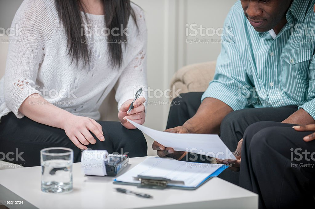 A husband and wife are sitting in their home looking over their...