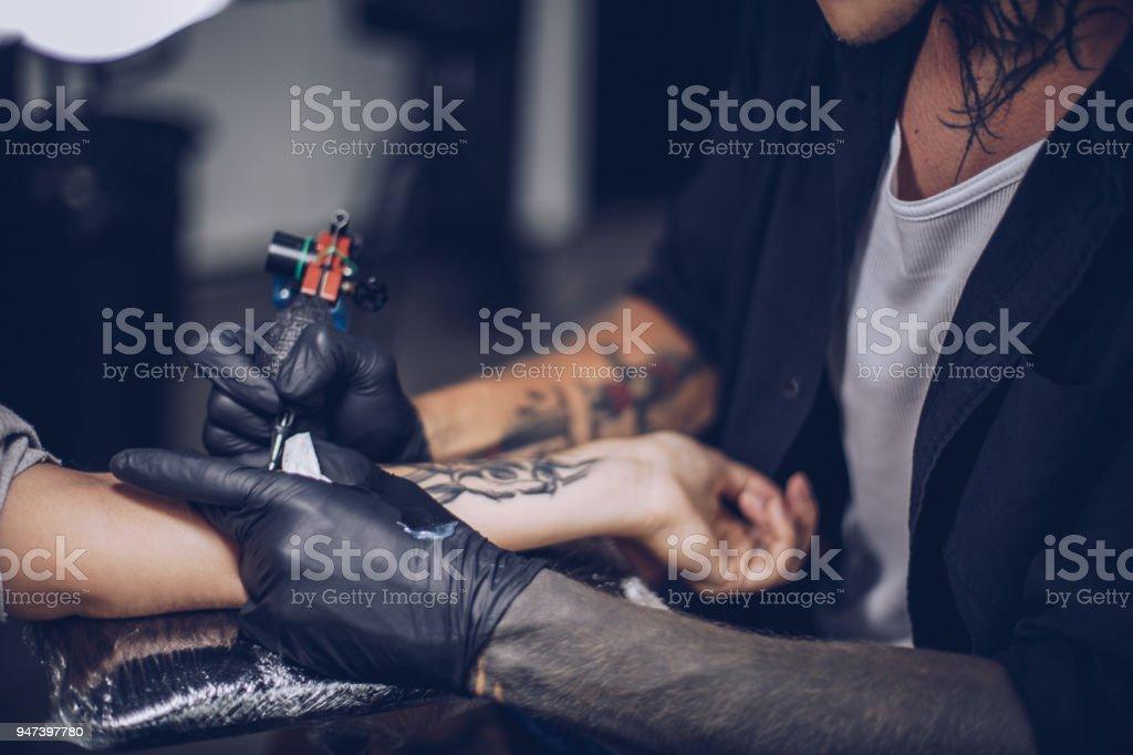 Getting arm tattoo stock photo