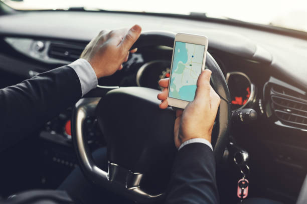 Getting around with the help of technology Closeup shot of an unrecognizable businessman using his cellphone while driving global positioning system stock pictures, royalty-free photos & images